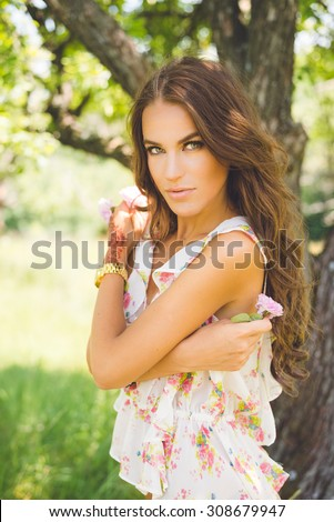 Portrait of amazing beautiful green eyed lady with gorgeous wavy hair and henna tattoo on her hand standing in garden on summer day outdoors background - stock photo