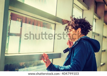 Portrait of American college student in New York. Wearing blue jacket with hood, a guy with freckle face, curly long hair, standing by glass wall on campus under sun, looking outside. Side View.   - stock photo