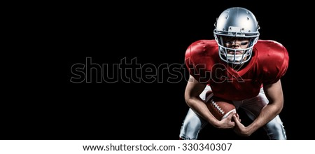Portrait of American football player bending while holding ball against black - stock photo