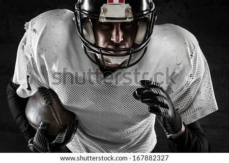 Portrait of american football player holding a ball and running - stock photo