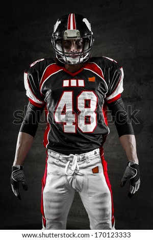 Portrait of american football player looking at camera on dark background - stock photo