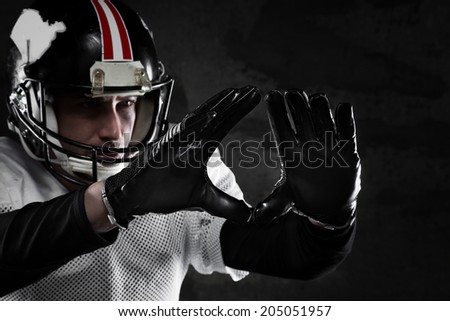 Portrait of american football player on dark background - stock photo