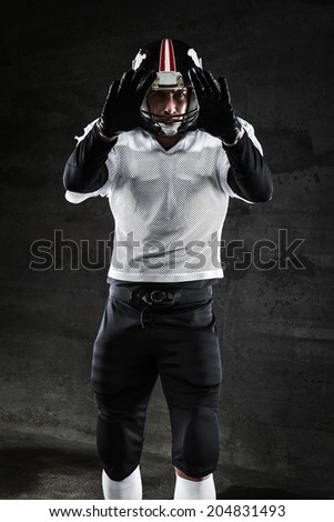 Portrait of american football player waiting� for ball - stock photo