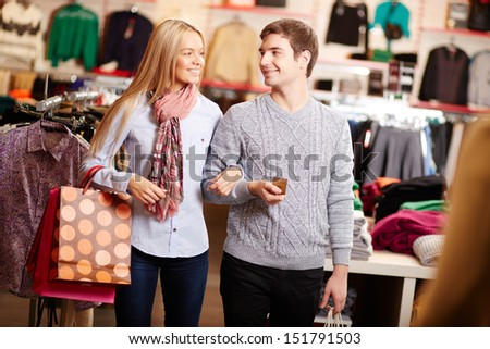 Portrait of amorous couple of shoppers interacting in clothing department - stock photo