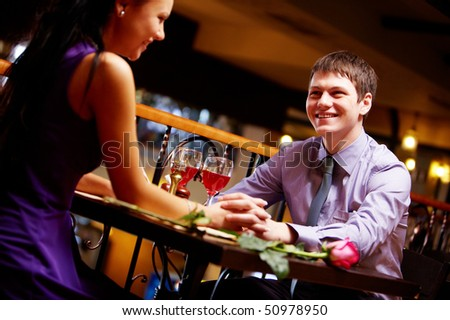 Portrait of amorous man and woman holding by hands in the cafe - stock photo