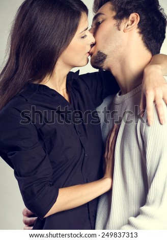 Portrait of amorous young couple embracing and kissing - stock photo