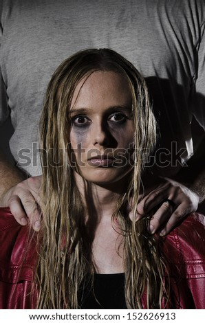 portrait of an abused woman with untidy hair and smudged makeup with a man standing behind her holding his hands on her shoulders cropped vertically - stock photo