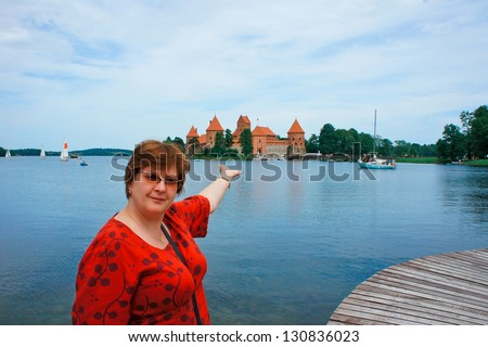 Portrait of an active middle-aged woman standing near the Castle on Lake Galve in Trakai, Lithuania - stock photo