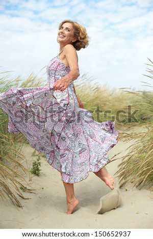 Portrait of an active older woman dancing at the beach - stock photo
