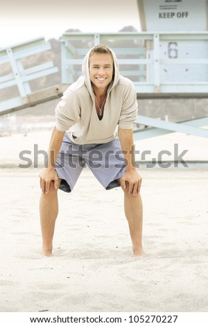 Portrait of an active young guy at the beach - stock photo