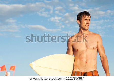 portrait of an active young man standing with a surfboard at the beach - stock photo