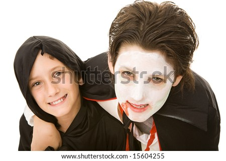 Portrait of an adolescent boy and his little brother, both dressed for Halloween.  Isolated on white. - stock photo