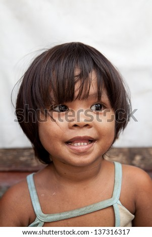 Portrait of an adorable Asian girl from impoverished area in the Philippines. - stock photo