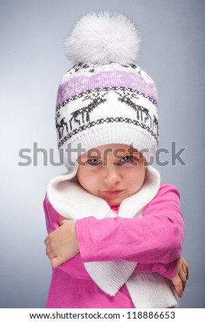Portrait of an adorable baby girl wearing a knit pink and white winter hat. - stock photo