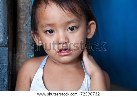 Portrait of an adorable Filipino girl living in poverty. Natural light. - stock photo