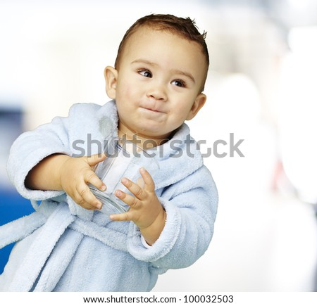 portrait of an adorable infant with a blue bathrobe holding a glass in his hand against an abstract background - stock photo