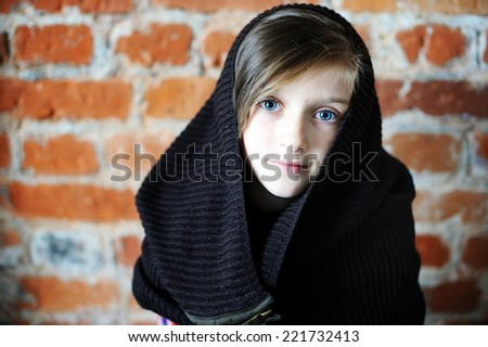 Portrait of an adorable kid girl with big blue eyes wearing fashion knitted dark brown snood on the bricks wall background - stock photo