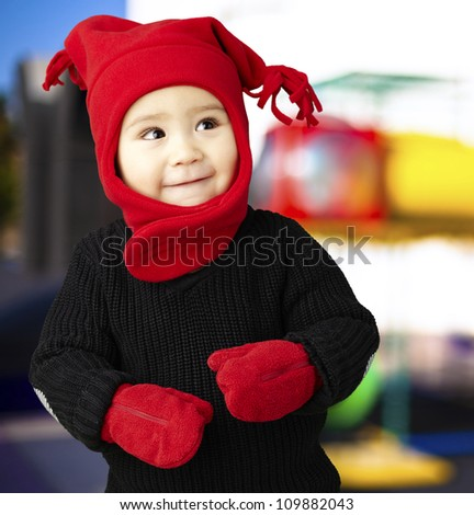 portrait of an adorable kid smiling and wearing winter clothes against an abstract background - stock photo
