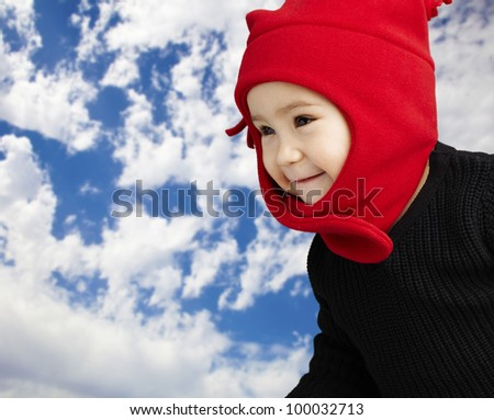 portrait of an adorable kid smiling wearing winter clothes against a cloudy background - stock photo