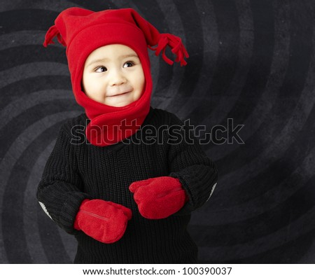 portrait of an adorable kid smiling wearing winter clothes against an abstract background - stock photo