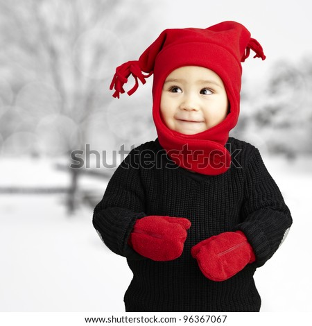 portrait of an adorable kid smiling wearing winter clothes at sn - stock photo