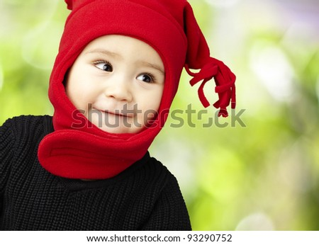 portrait of an adorable kid smiling wearing winter clothes at the park - stock photo