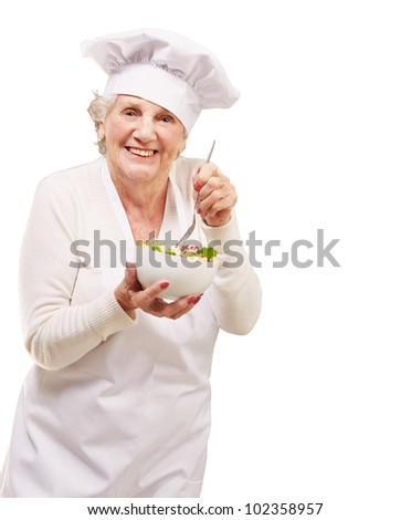 portrait of an adorable senior cook woman eating a salad against a white background - stock photo