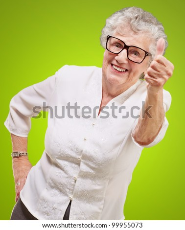 portrait of an adorable senior woman doing a good gesture over a green background - stock photo