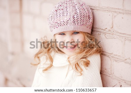 Portrait of an adorable toddler girl wearing fashion knitted clothes, a sweater and hat in pink and white - stock photo