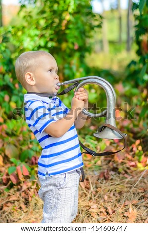 portrait of an adorable toddler playing on a silver trumpet  - stock photo