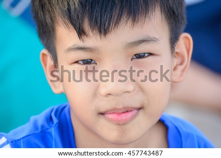 Portrait of an adorable young  boy with black hair In the mood to depression. - stock photo