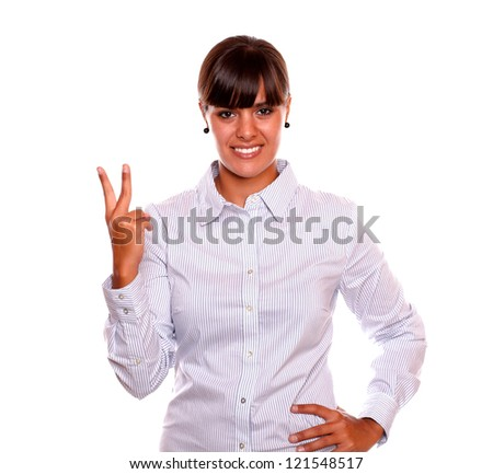 Portrait of an adult business woman holding up two fingers in victory sign on isolated background - stock photo