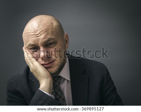 Portrait of an adult man in a business suit on a black background. Man with a toothache tooth pain - stock photo