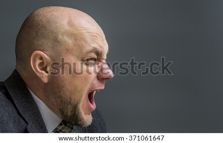 Portrait of an adult man in a business suit on a black background. Side profile portrait of angry man screaming  - stock photo