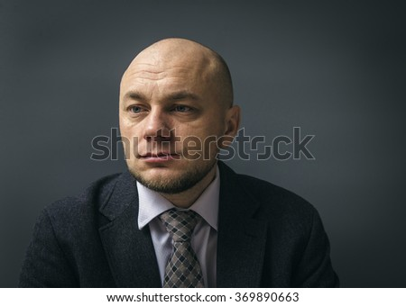 Portrait of an adult man in a business suit on a black background. Unhappy and thoughtful businessman. - stock photo