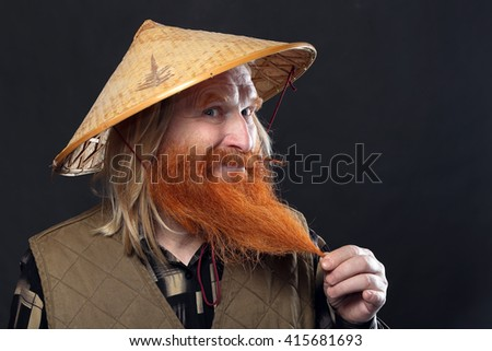 Portrait of an adult man with a red beard and mustache in the Vietnamese hat on a dark background studio - stock photo