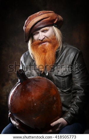 Portrait of an adult man with a red beard and mustache with bottle on a dark background studio - stock photo