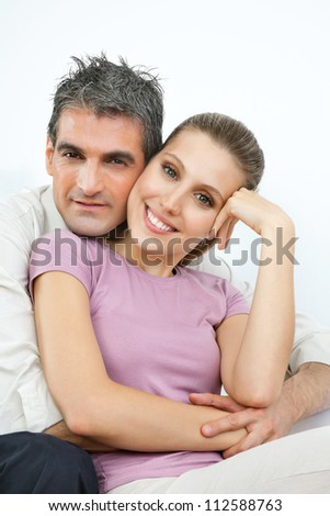 Portrait of an affectionate couple embracing over white background - stock photo