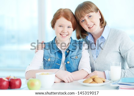 Portrait of an affectionate mother and her daughter smiling at the viewer - stock photo
