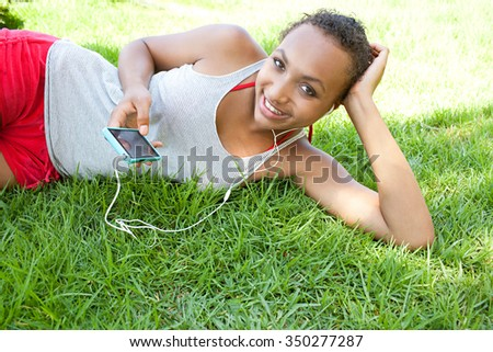 Portrait of an african american black teenager girl laying on green grass in a park, relaxing listening to music using a smartphone and headphones, smiling outdoors. Adolescent technology lifestyle. - stock photo
