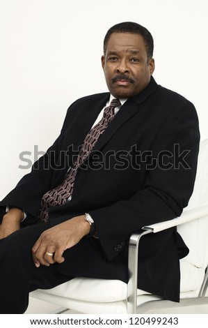 Portrait of an African American confident businessman sitting on chair isolated over white background - stock photo