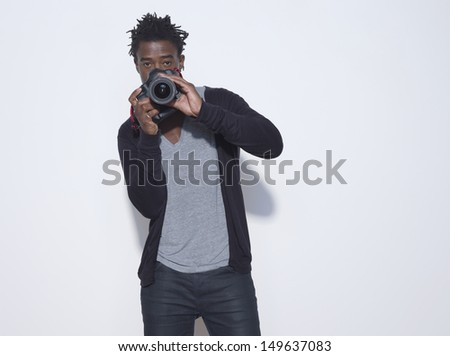 Portrait of an African American male photographer holding camera in studio - stock photo