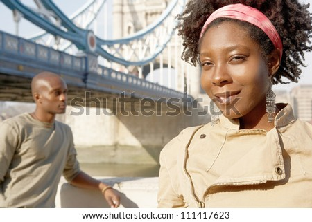 Portrait of an african american man and woman standing by Tower Bridge while sightseeing in London. - stock photo