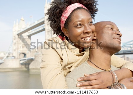 Portrait of an african american tourist couple visiting the Tower of London overlooking the river, being joyful. - stock photo