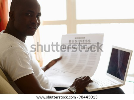 Portrait of an African American with newspaper and laptop - stock photo