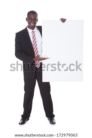 Portrait Of An African Businessman Presenting Blank Placard - stock photo