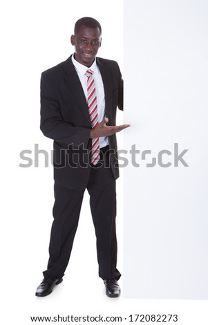 Portrait Of An African Businessman Presenting Blank Placard Over White Background - stock photo