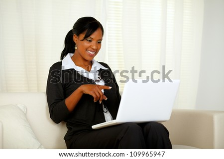 Portrait of an afro-American businesswoman on black suit pointing to laptop screen while sitting on sofa at home indoor - stock photo