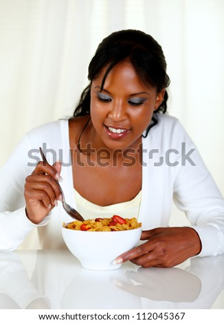 Portrait of an afro-american woman eating a bowl of cereals with strawberries at soft colors composition - stock photo