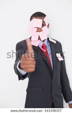 Portrait of an Afro businessman covered in blank notes gesturing thumbs up over white background - stock photo
